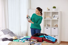 De reiszak van de vrouwenverpakking thuis of hotelruimte Stock Fotografie