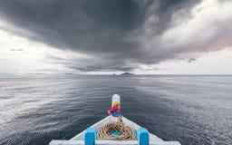 De reizende boot gaat naar eiland terwijl het regenen strom dichtbij komt stock foto's