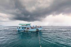 De reizende boot met passagier gaat naar eiland terwijl het regenen strom dichtbij komt royalty-vrije stock foto