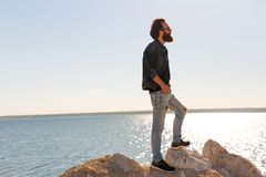 De reiziger bevindt zich op een rots tegen mooie overzeese vreedzame golven, het modieuze gebaarde hipsterjongen stellen dichtbij royalty-vrije stock foto's