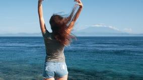 De reiziger geniet van mening van oceaan, bergen De opwinding van het meisjeshaar in wind, langzame motie stock videobeelden