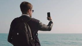 De reiziger met rugzak is status, in openlucht nemend foto van overzees door smartphone stock footage