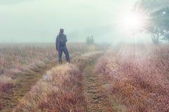 De reiziger op de herfst mistige weide bekijkt op helder zonlicht Royalty-vrije Stock Foto's