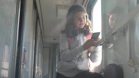 De reiziger van het tienermeisje met rugzak bevindt zich door het venster van de treinauto met een smartphone Reisvervoer stock footage