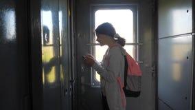 De reiziger van het tienermeisje met rugzak bevindt zich door het venster van de treinauto met een smartphone Reisvervoer stock video