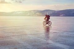 De reiziger van de ijsfietser met rugzakken op fiets op ijs van Meer Baikal Tegen de achtergrond van zonsonderganghemel, ijsopper Stock Afbeelding