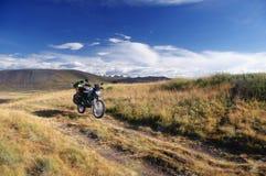 De reiziger van motorfietsenduro alleen onder een blauwe hemel met witte wolken op een achtergrond van bergen met sneeuwijs behan Royalty-vrije Stock Afbeeldingen