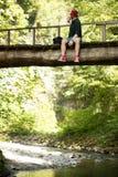 De reiziger zit op houten brug en gebruikt smartphone om kaart te zien voor het navigeren royalty-vrije stock afbeelding