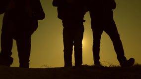 de reizigers beklimmen de heuvel ??n voor ??n in de stralen van de zon Toeristenreis met rugzakken Groepswerk van bedrijfsmensen stock videobeelden