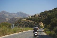 De reizigers koppelen op autoped die een bergweg berijden Het eiland van Kreta, Griekenland stock afbeelding