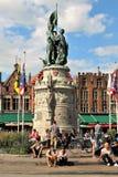 De reizigers rusten dichtbij het standbeeld