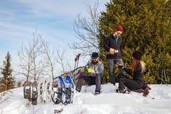 De reizigers rusten in de winter in de bergen Het bedrijf van jongeren op een halt stock foto