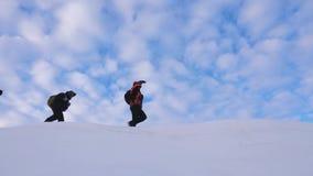 De reizigers volgen elkaar langs de sneeuwrand Gecoördineerd groepswerktoerisme in de winter Een team van klimmers in stock video