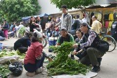De reizigers vragen om het kopen van groene groenten op een straatmarkt in Vietnam Stock Foto