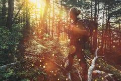 De reizigersmens met rugzak loopt door het bos en geniet van de mening van de zon Concept avontuur, wandeling en ontdekking stock fotografie