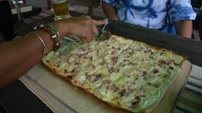 De reizigersmensen die pizza dun korst snijden voor eten bij restaurant stock video