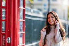 De reizigersvrouw die van Londen aan haar mobiele telefoon spreken stock afbeeldingen