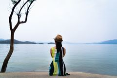 De reizigersvrouw geniet van bekijkend mooi meer met bergen op achtergrond royalty-vrije stock afbeeldingen