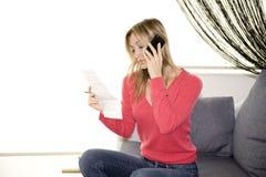 De rekening van de lezing en het spreken op cellphone stock foto