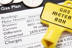 De rekening van het gas met metersleutel en muntstukken Stock Afbeeldingen