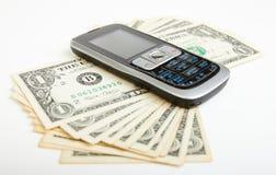 De rekeningen van de dollar en mobiele telefoon Stock Foto's