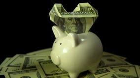 De rekeningen van het spaarvarken en van de dollar zetten een zwarte achtergrond aan stock video