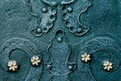 De in reliëf gemaakte metaal groenachtig blauwe achtergrond met barokke details en met het goud van het knopenmetaal bloeit Stock Fotografie