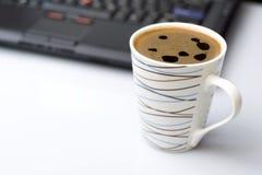 De rem van de koffie in bureau en laptop op een bureau Stock Foto's