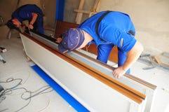 De Reparatie van de garagedeur Contractant die weatherproofing van de garagedeur de verbinding van de garagedeur installeren Verv royalty-vrije stock foto