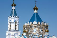 De reparatie van de Orthodoxe Kerksteiger op de toren, een blauw dak en een blauwe hemel Stock Afbeeldingen