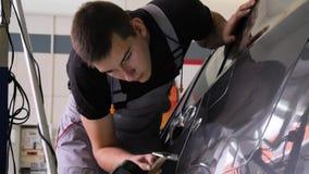 De Reparatieverwijdering van de Paintlessdeuk Kraan onderaan rubber de hamer autolichaam van de hulpmiddelendeuk De kerelslagen m stock footage