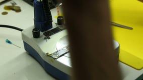 De reparatiewerkplaats voert reparatie van smartphones uit stock video