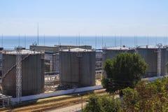 De reservoirs van de olieopslag op de kust in haven stock foto