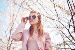 De ressort de mode de fille portrait dehors dans les arbres de floraison Femme romantique de beauté en fleurs dans des lunettes d Images libres de droits