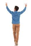 De retour d'un homme marchant avec des mains composant la victoire photos stock