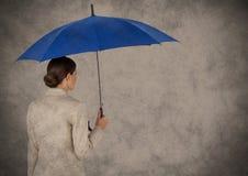 De retour de la femme d'affaires avec le parapluie contre le fond et le recouvrement bruns de grunge Images stock