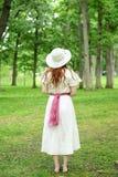 De retour de la femme rousse de vintage avec le chapeau en parc photographie stock