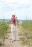 De retour du chapeau de port de femme sur le chemin de plage photos stock