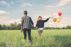 De retour de jeunes couples asiatiques heureux tenant le togeth de ballon et de promenade Photos stock