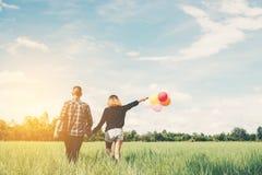 De retour de jeunes couples asiatiques heureux tenant le togeth de ballon et de promenade Photo libre de droits