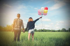 De retour de jeunes couples asiatiques heureux tenant le togeth de ballon et de promenade Photos libres de droits