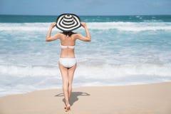 De retour de la jeune femme dans le bikini se tenant sur la plage, jeune belle femme sexy dans le maillot de bain de bikini, île  photographie stock libre de droits
