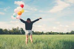 De retour de la jeune femme heureuse se tenant sur le champ vert appréciez avec le fre photo stock
