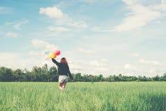 De retour de la jeune femme heureuse se tenant sur le champ vert appréciez avec le fre image libre de droits