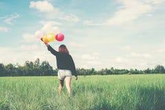 De retour de la jeune femme heureuse se tenant sur le champ vert appréciez avec le fre photos stock