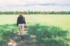 De retour de la jeune femme portant le rétro appareil-photo dans le domaine d'herbe appréciez t images stock