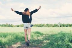 De retour de la jeune femme portant le rétro appareil-photo dans le domaine d'herbe appréciez t photo stock