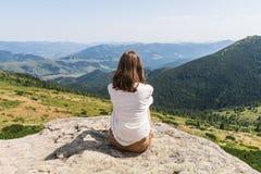 De retour de la jeune personne féminine s'asseyant sur la roche en montagnes carpathiennes ukrainiennes Photo stock