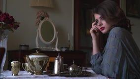 In de retro flat zit een meisje bij de lijst en heeft ontbijt stock footage