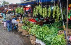 De reusachtige bossen van gigatslabonen hangen op de teller in de Indonesische straatmarkt stock foto's
